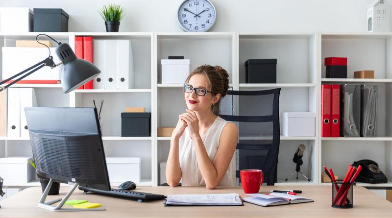 一个年轻女孩坐在办公室的桌子旁。