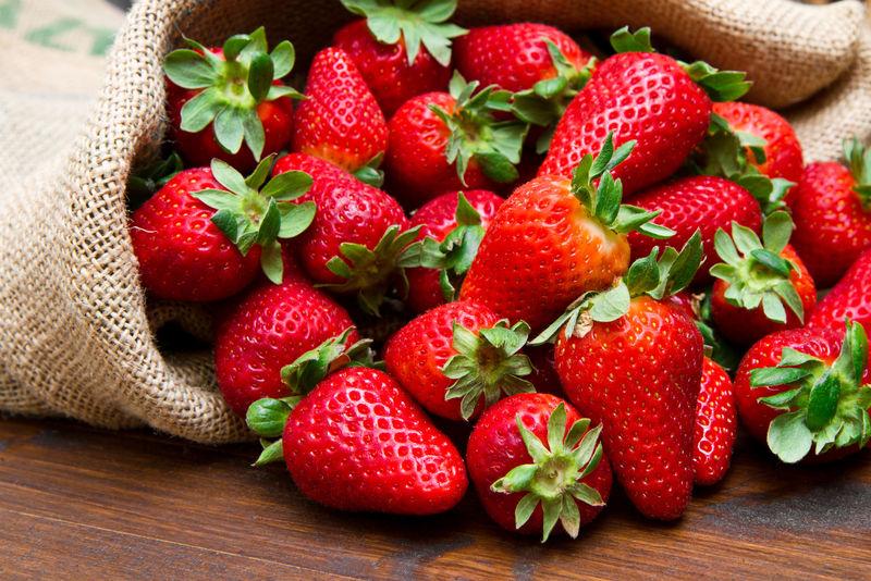 在麻袋的木材新鲜草莓