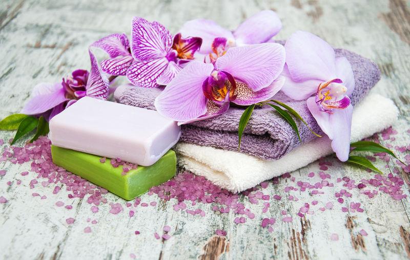 旧木桌上的手工肥皂和紫色兰花