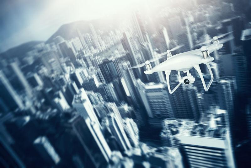图为白色哑光通用设计遥控空中无人机与行动相机下的城市天空飞行。现代大都市背景。水平,正面视图。运动模糊效果。三维渲染。