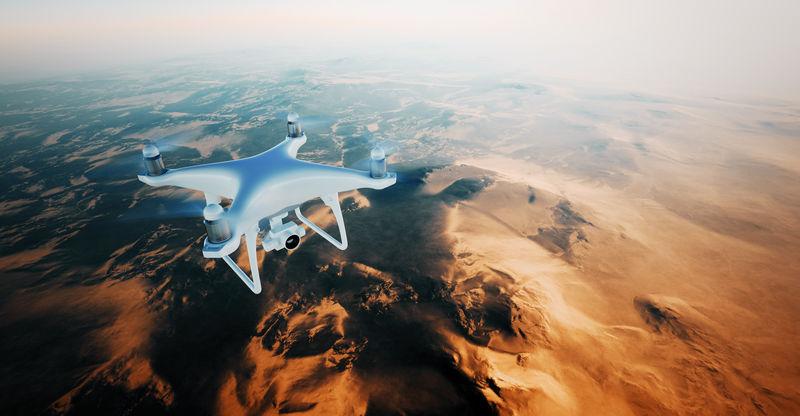 图为白色哑光通用设计空中无人机在地表下飞行。无人居住的沙漠山脉日落背景。水平,前顶角视图。电影效果。三维渲染。