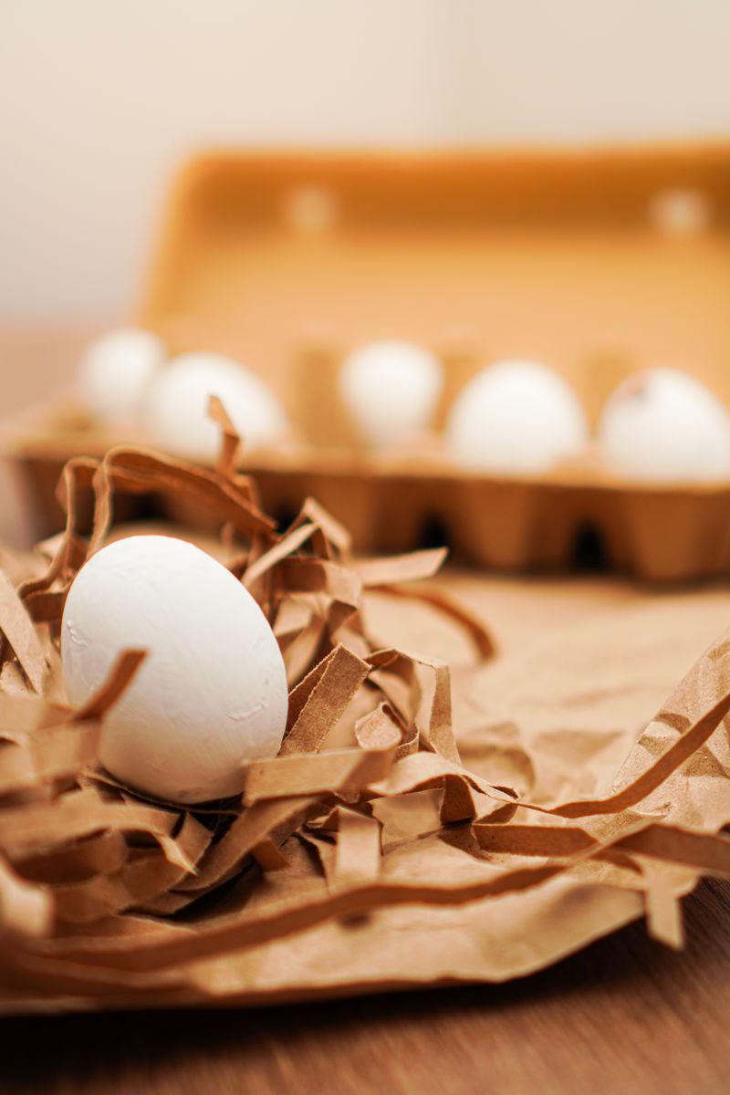 复活节,棕色纸上的白鸡蛋和木制小报上的蛋盘