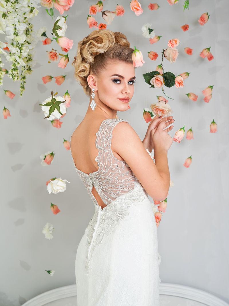 美丽的金发新娘穿着婚纱在花丛中