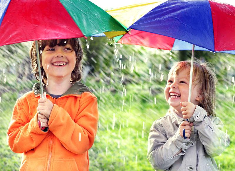 两个快乐的兄弟带着雨伞在户外
