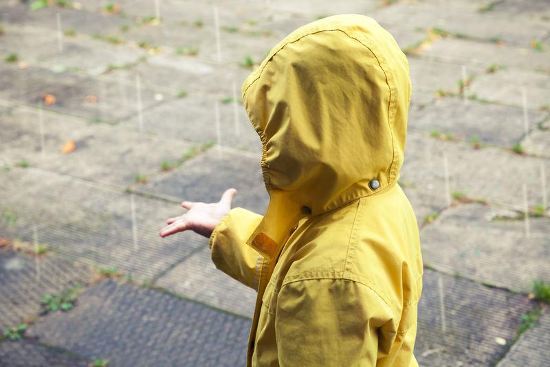 穿着黄色雨衣玩雨滴的小孩