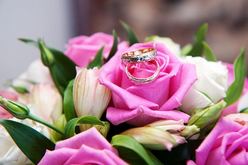 新娘花束背景上的两枚金结婚戒指