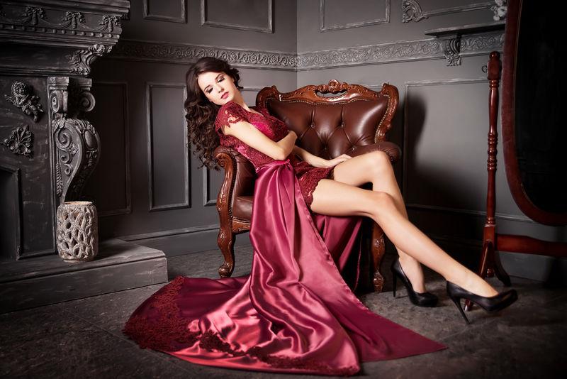 女人坐在椅子上长的红葡萄酒,紫色的连衣裙。豪华
