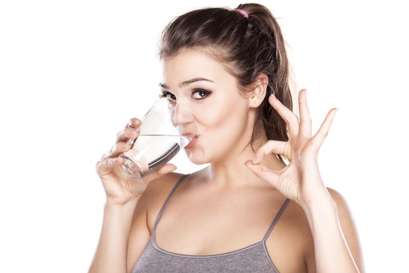 美女从杯子里喝水,表现出美味。