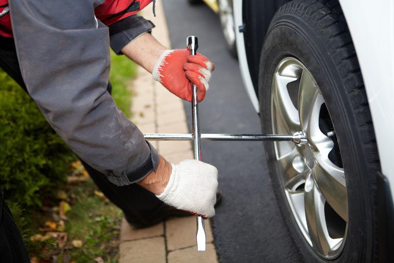 汽车修理工换轮胎。