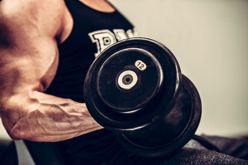 一个年轻人在健身馆用哑铃健身