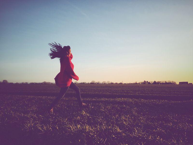 快乐的女人跳过田野