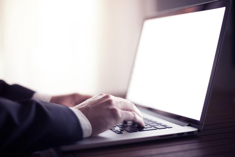 一个商人在用黑屏笔记本电脑工作