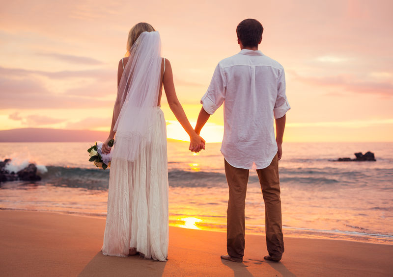 新婚夫妇,新郎新娘在美丽的热带日落