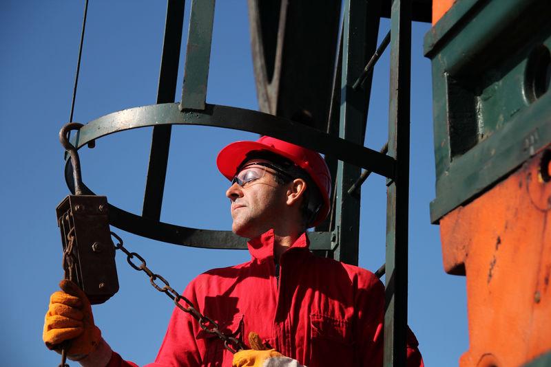 石油工业工人使用链式绞车。