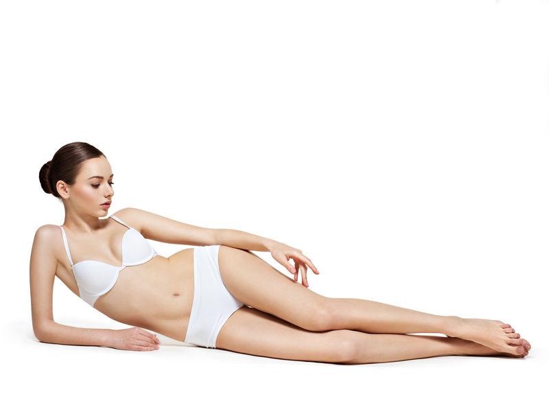 美丽的女人躺在白色的身体上