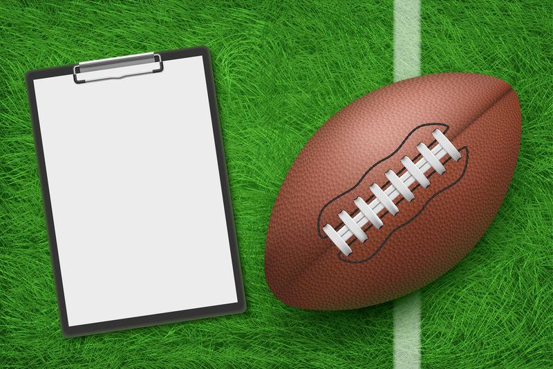 橄榄球和剪贴板在球场绿草地上