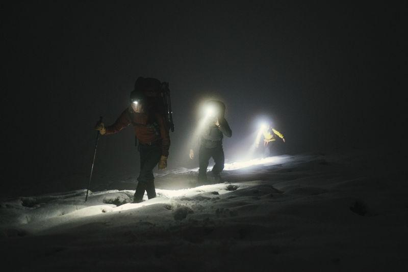 苏格兰格伦科的登山者在寒冷的夜晚徒步旅行