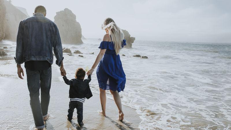 快乐的一家人一起在海滩散步