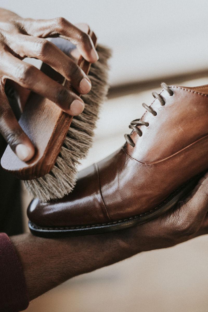 在棕色皮鞋上涂鞋油的人