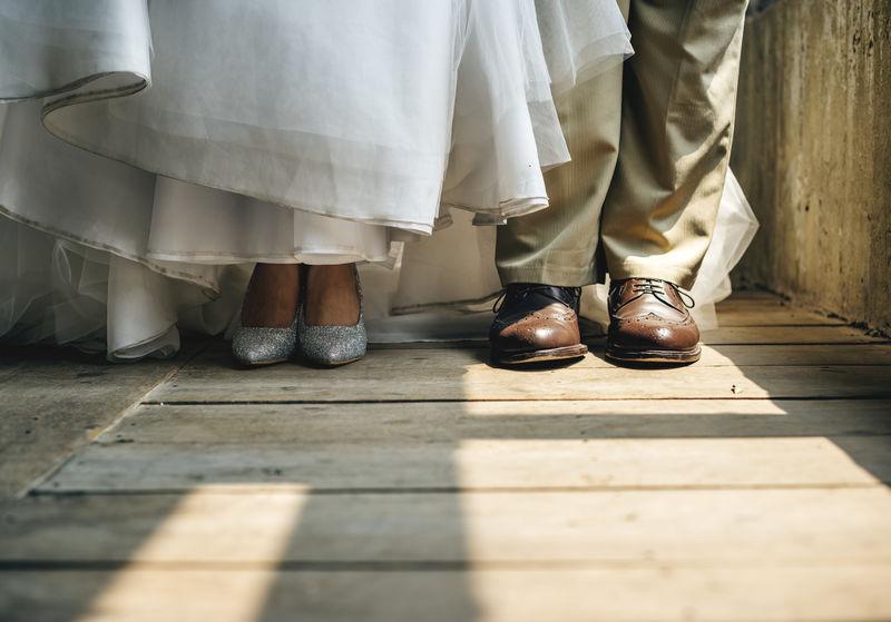 新郎新娘脚站在木地板上