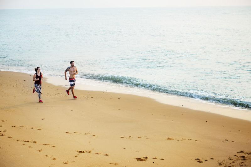 健康的年轻夫妇一起在海边跑步