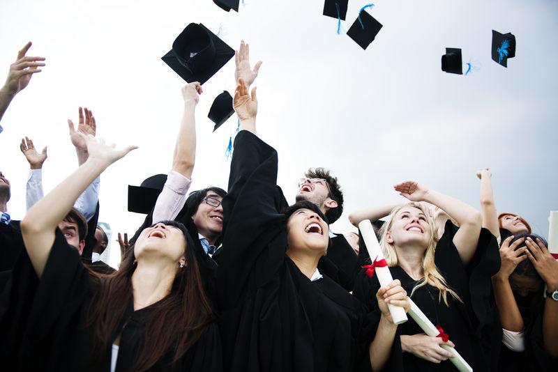 一群形形色色的毕业生向天空扔帽子