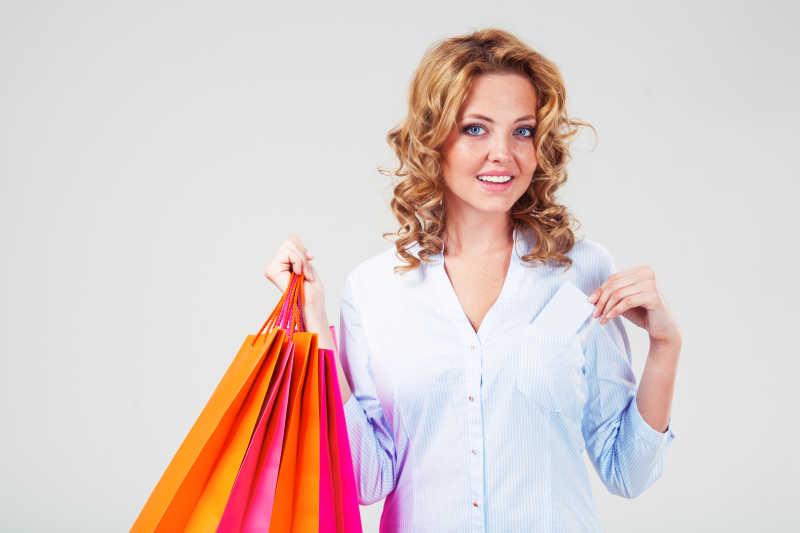 拎着购物袋从口袋拿出信用卡的女人