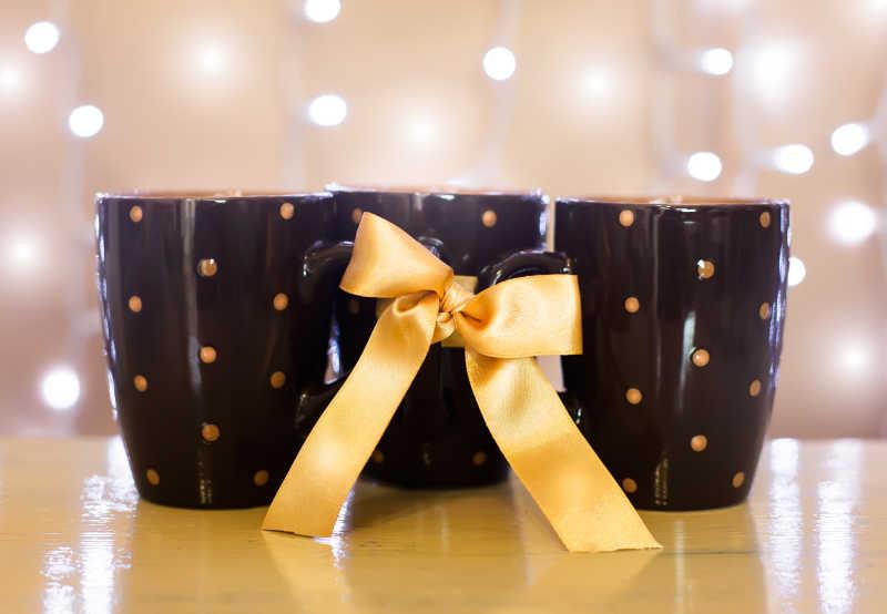 藕色背景下黄色桌上的扎着蝴蝶结的三个黑色咖啡杯