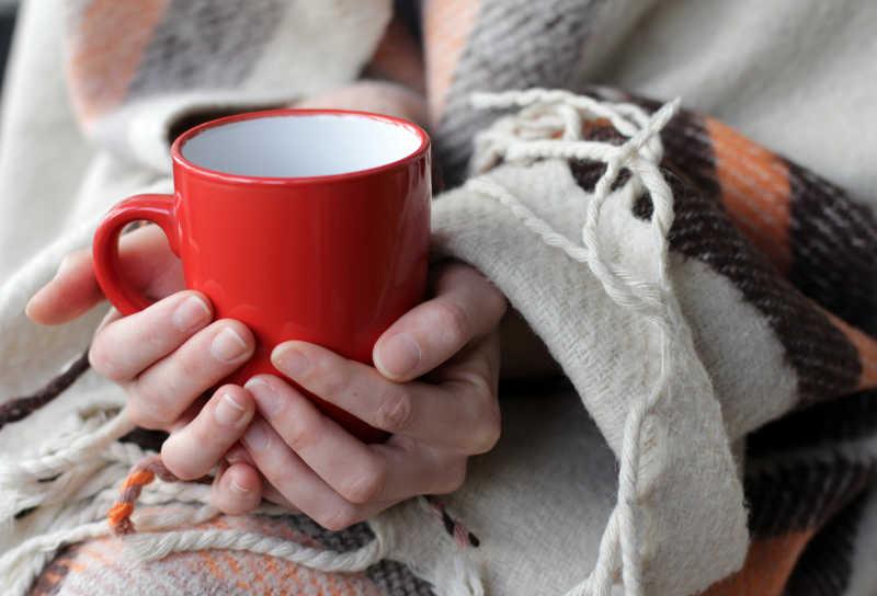 双手捂着红色咖啡杯取暖的美女