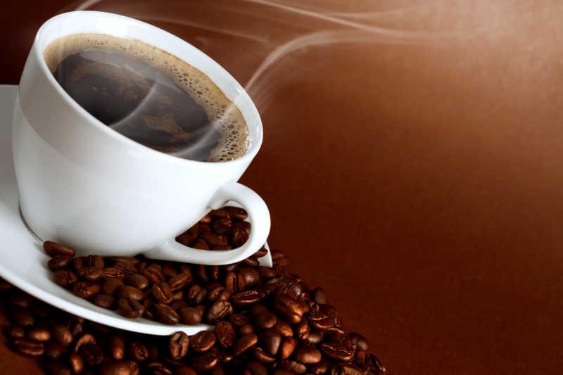 褐色背景下一堆咖啡豆中间的一杯热咖啡