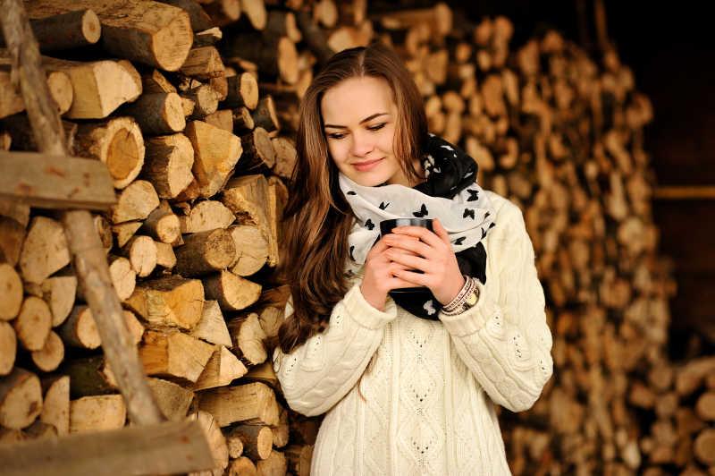 站在一堆木头前拿着杯子暖手的美女