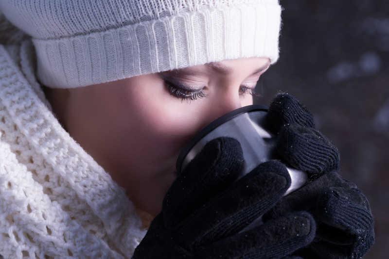 黑色背景下双手端着咖啡杯喝咖啡的女人