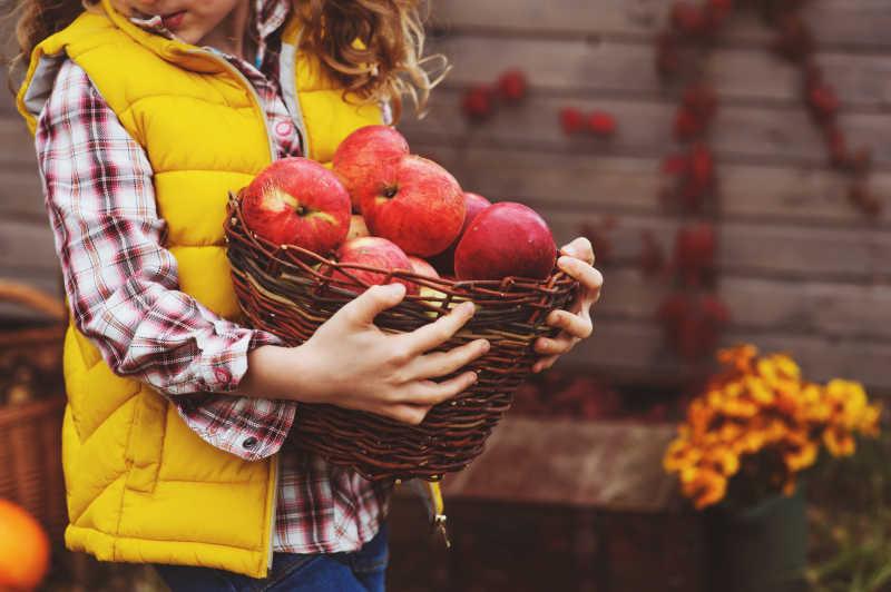 女孩手里抱着一篮子苹果