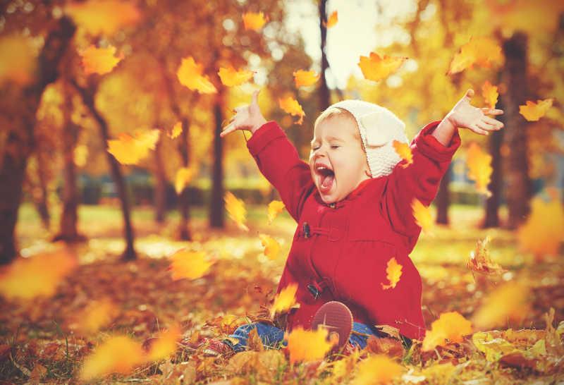 阳光下秋天的公园里坐在落叶上的小女孩