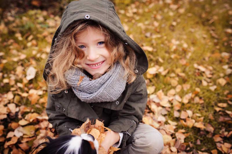 秋天坐在草地上抓着树叶的小孩子