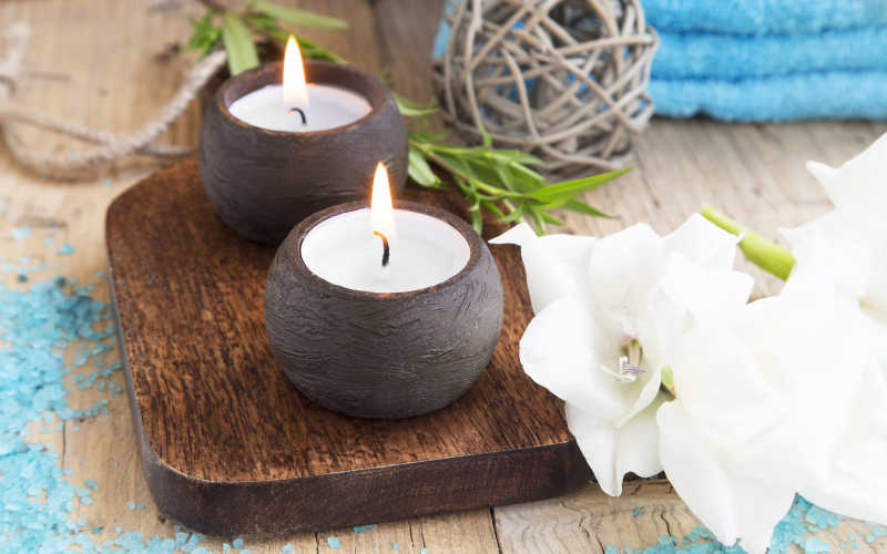 木板上燃烧的蜡烛和旁边的百合花