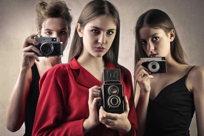 拿着照相机的三个美女