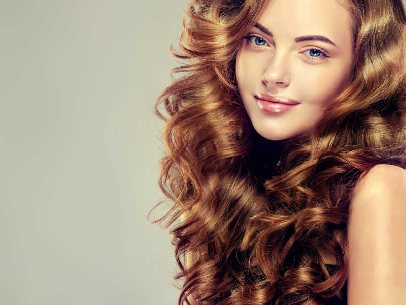 戴着珠宝耳环的长波浪的黑色卷发的漂亮女孩
