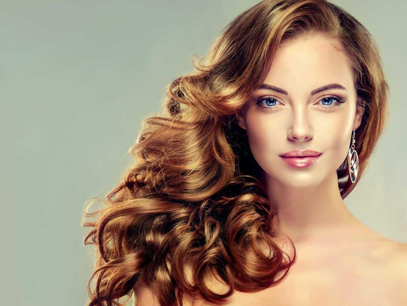 戴着珠宝耳环的黑色的长波浪卷发的漂亮女孩