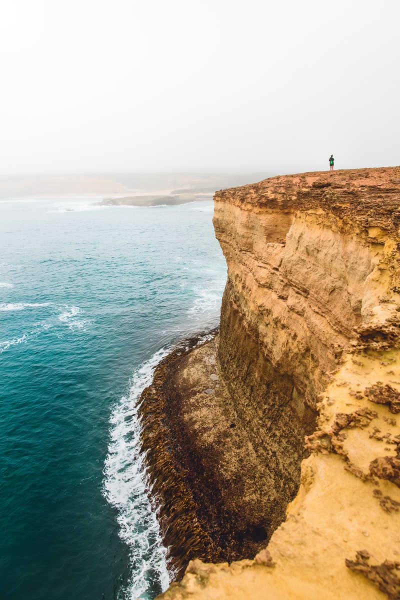 站在海边悬崖上的人