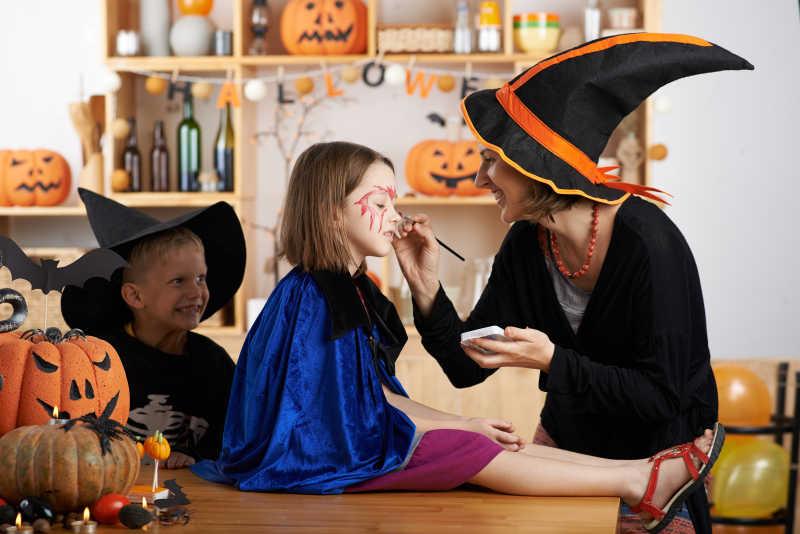 万圣节背景下老师为孩子们化妆