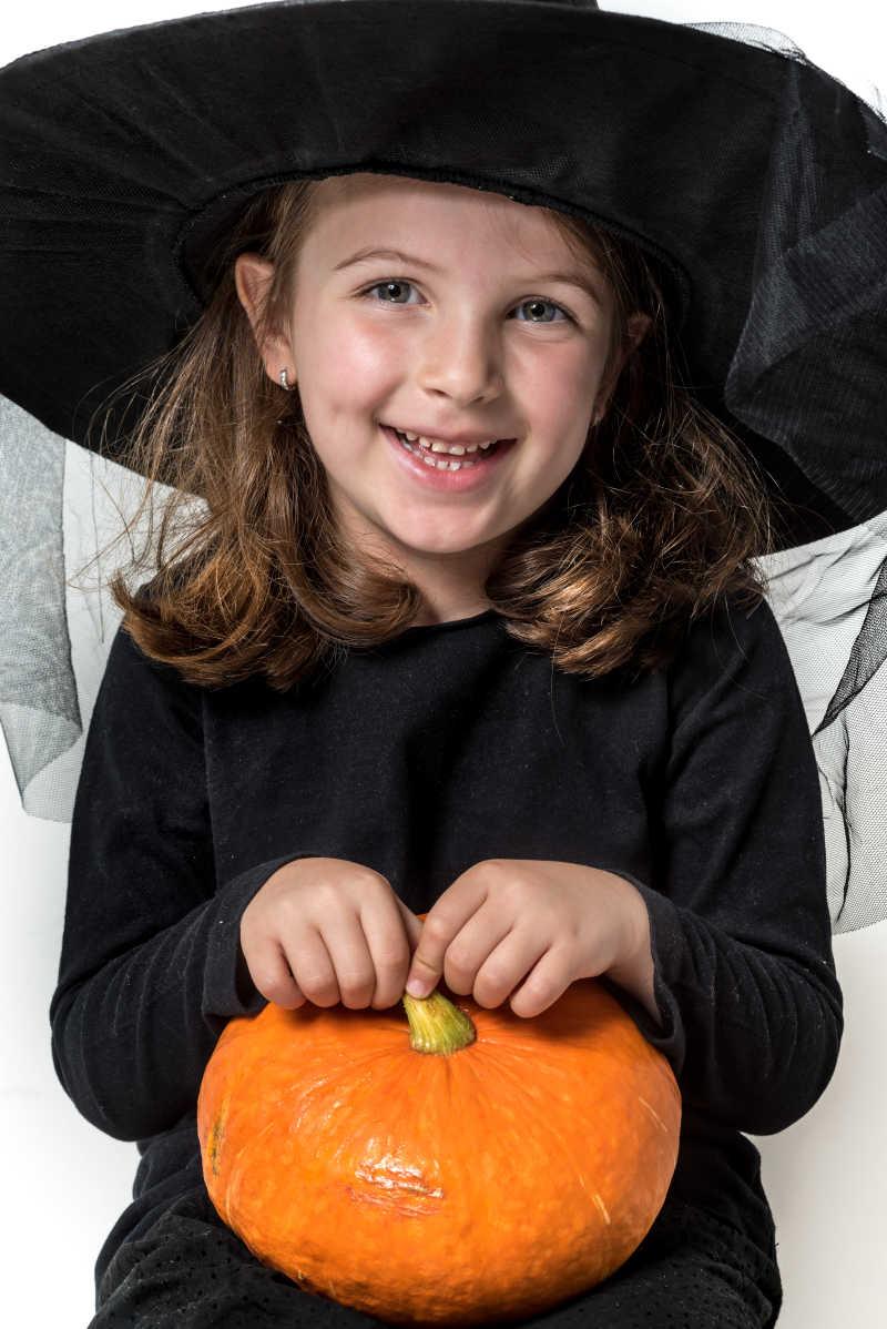 白色背景下女巫装扮的小女孩抱着南瓜灯