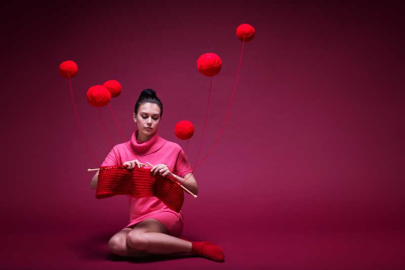 年轻的外国美女在用红色线球织毛衣