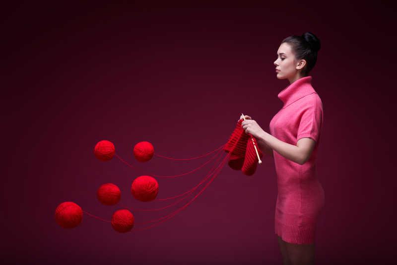 美女在用六个红色毛线织毛衣