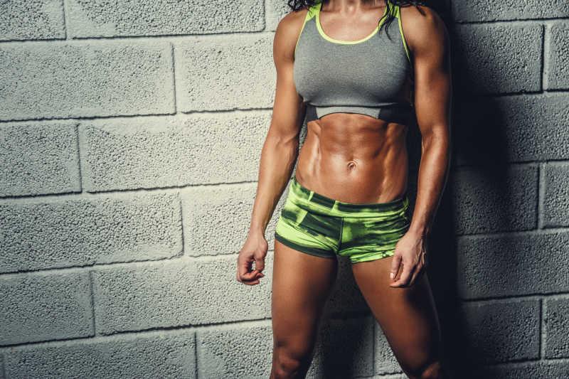 在灰色背景下的肌肉女子