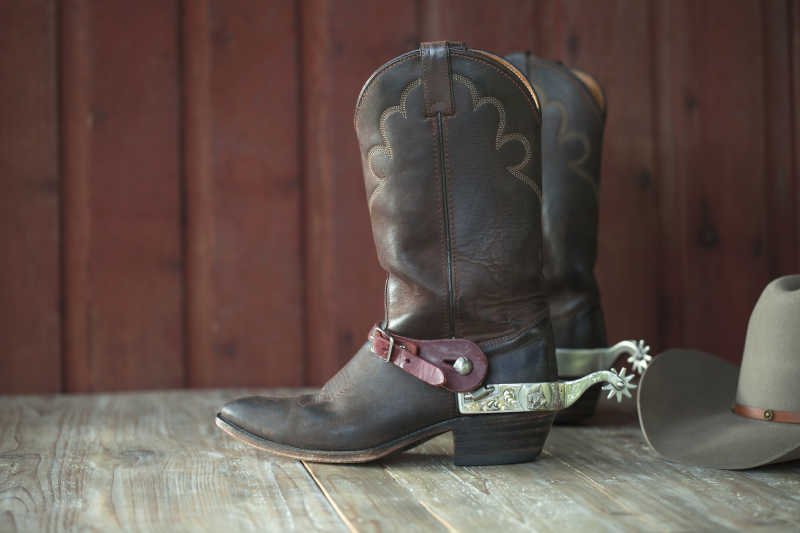 木制背景下的牛仔靴和帽子