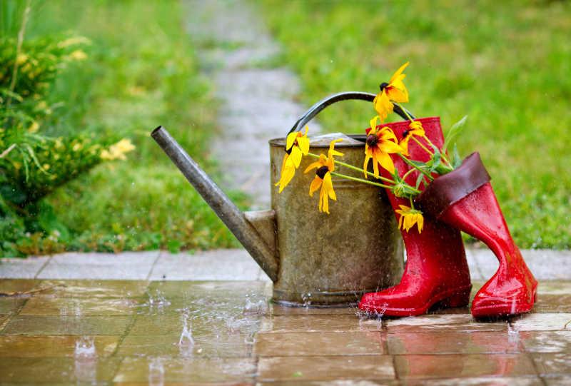草地背景下插着鲜花的红色雨鞋