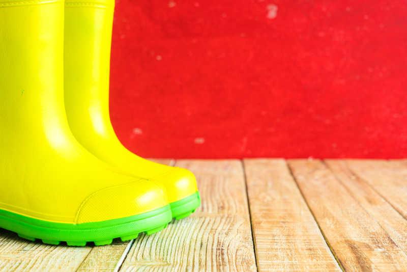 木制背景下的黄色雨靴