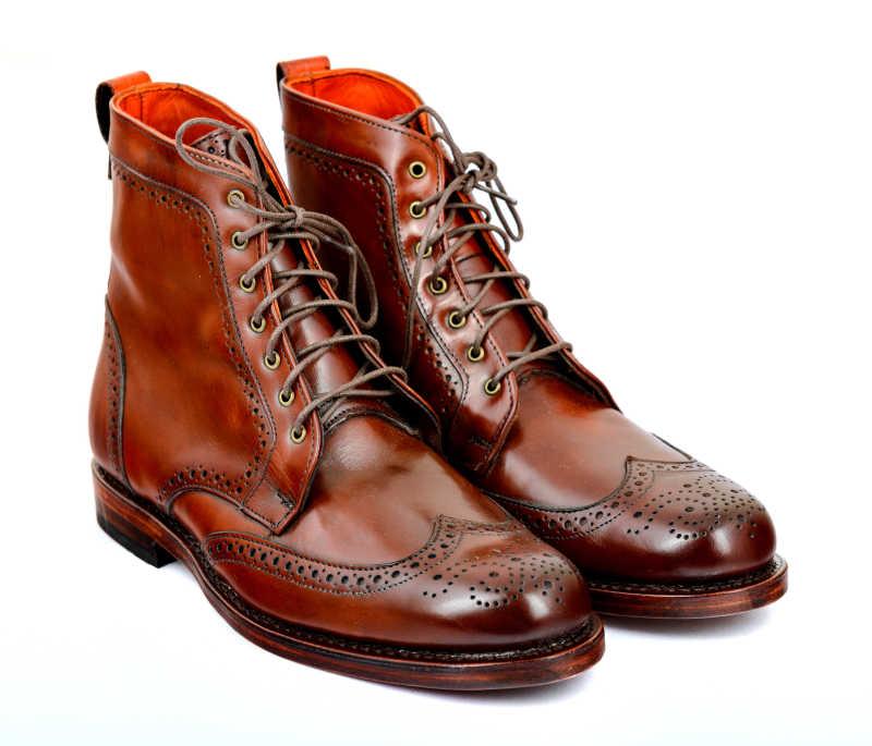 白色背景下的棕色绑鞋带皮鞋