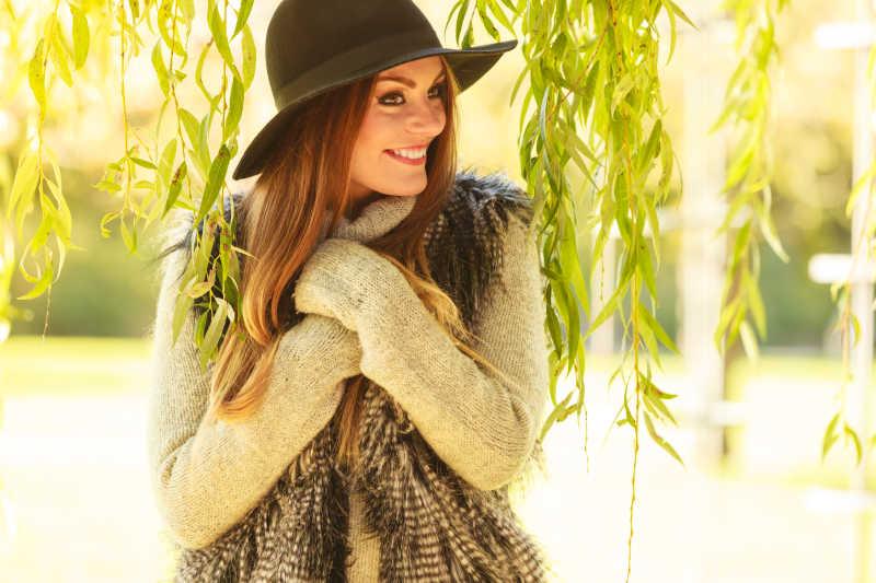 漂亮的年轻女子穿着时髦的毛衣和帽子温暖自己在户外